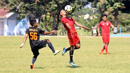 Salah satu pemain Persis Solo (merah) berebut bola dengan pemain PS UNS dalam uji coba di Lapangan AURI Lanud Adi Soemarmo, Karanganyar, Sabtu (06/04/19). - INDOSPORT