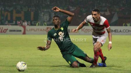 Aksi pemain Persebaya, Amido Baldé dijaga ketat pemain Madura United, Jaimerson Xavier. Foto: Fitra Herdian/Indosport.com - INDOSPORT