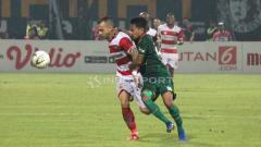 Indosport - Pemain Madura United, Aleksandar Rakic mencoba melewati hadangan dari pemain Persebaya. Foto: Fitra Herdian/Indosport.com