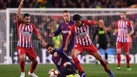 Lionel Messi berusaha keras untuk mengamankan bola dari Rodri pada laga Laliga Spanyol di Camp Nou pada Minggu (07/04/19). Alex Caparros / Getty Images