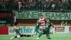 Indosport - Sambil menjatuhkan diri bola cocoran bek Persebaya Hansamu Yama Pranata (kanan) tak bisa dihentikan Muhammad Ridho, kiper Madura United, meluncur deras ke gawang yang kosong. Satu gol Hansamu memastikan Persebaya menang 3-2 atas Madura Unted.