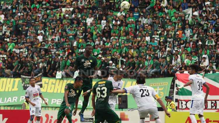 Duel udara para pemain Persebaya melawan Arema FC. Fitra Herdian/INDOSPORT Copyright: Fitra Herdian/INDOSPORT