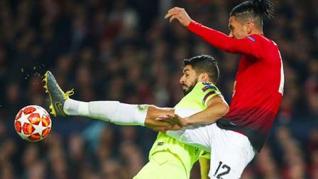 Pemain Manchester United, Chris Smalling saat berduel udara dengan Luis Suarez di laga Manchester United vs Barcelona. Foto: Robbie Jay Barratt - AMA/Getty Images