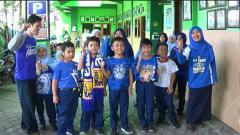 Indosport - Antusiasme siswa siswi SD Muhammadiyah 1 Kota Malang saat mengenakan atribut Arema.