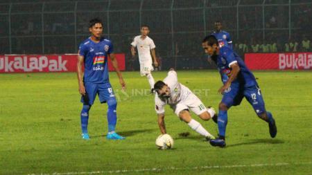 Damian Lizio (tengah, putih) bersusah payah mencoba merebut bola dari kaki pemain Arema FC (Fitra Herdian/INDOSPORT) - INDOSPORT