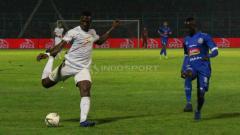 Indosport - Striker Persebaya, Amido Balde (kiri putih) mendapat pengawalan dari pemain Arema FC, Makan Konate (Fitra Herdian/INDOSPORT).