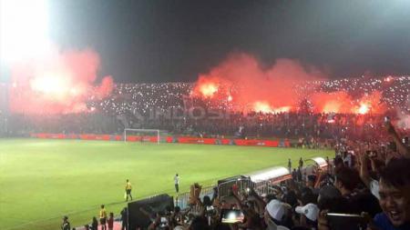 Nyala flare di salah satu tribun Stadion Kanjuruhan. - INDOSPORT