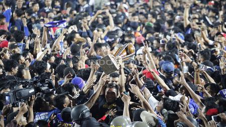 Pemain Arema FC mengangkat trophy Piala Presiden 2019 ditengah ribuan Aremania di stadion Kanjuruhan, Jumat (12/04/19). Foto: Herry Ibrahim/INDOSPORT - INDOSPORT