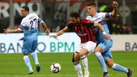 Hakan Calhanoglu berusaha mempertahankan bola dari pemain Lazio, Minggu (14/04/19), di San Siro - INDOSPORT