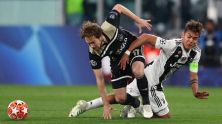 Paulo Dybala kesulitan untuk melewati hadangan Daley Blind. - INDOSPORT