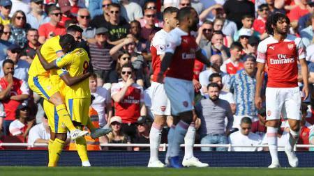 Christian Benteke melakukan selebrasi bersama Scott Dann dan Cheikhou Kouyate usai cetak gol ke gawang Arsenal di Emirates Stadium, Senin 21/04/19. Warren Little/Getty Images - INDOSPORT