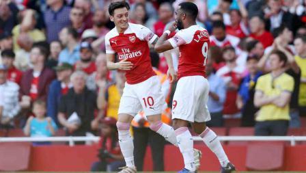 Mesut Ozil merayakan gol bersama Alexandre Lacazette pada laga Liga Primer Inggris di Emirates Stadium, Senin 21/04/19. Clive Rose/Getty Images