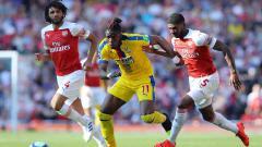 Indosport - Wilfried Zaha dikawal ketat pemain Arsenal Ainsley Maitland-Niles dan Mohamed Elneny pada laga laga Liga Primer Inggris di Emirates Stadium, Senin 21/04/19. Warren Little/Getty Images