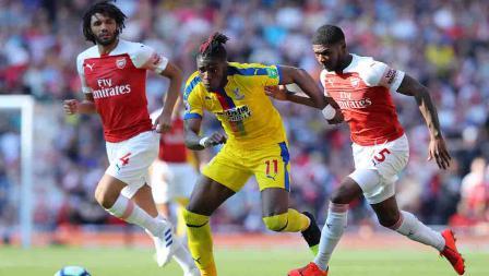 Wilfried Zaha dikawal ketat pemain Arsenal Ainsley Maitland-Niles dan Mohamed Elneny pada laga laga Liga Primer Inggris di Emirates Stadium, Senin 21/04/19. Warren Little/Getty Images