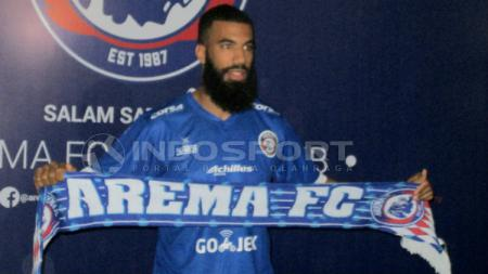 Sylvano Comvalius membentangkan syal Arema FC saat perkenalannya di Kantor Arema, Rabu (24/04/19). - INDOSPORT