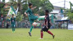 Indosport - Pemain Persebaya U-16 berusaha melewati pemain Persipura U-16, pada laga perdana Pro Elite Academy. Minggu (28/4/19). Fitra Herdian/INDOSPORT.