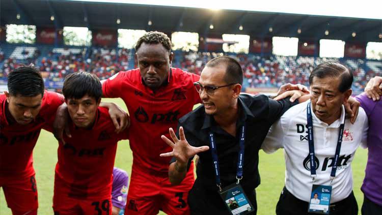 Pemain PTT Rayong Victor Igbonefo (tengah) saat mendengarkan instruksi pelatih. Copyright: Facebook/PTTRY