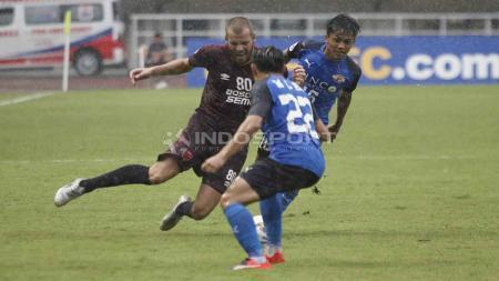 Wiljan Pluim saat akan mengeksekusi bola dari serangan dua pemain Home United. Herry Ibrahim/INDOSPORT - INDOSPORT