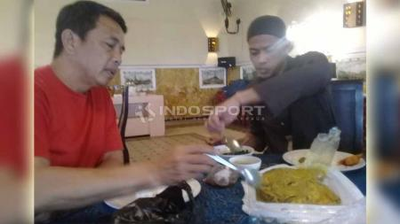 Jandia Eka Putra saat mencoba memakan kepala ikan kakap bersama pelatih Jafri Sastra. Foto: Ronald Seger Prabowo/INDOSPORT - INDOSPORT