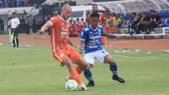 Indosport - Pemain Persib, Ghozali Siregar berusaha merebut bola dari pemain Borneo FC pada laga Persib Bandung vs Borneo FC di Stadion Si Jalak Harupat, Kabupaten Bandung, Sabtu (04/05/2019). Foto: Arif Rahman/INDOSPORT