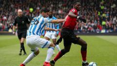 Indosport - Paul Pogba menjaga bolanya dari lawan di pertandingan Liga Primer Inggris antara Huddersfield vs Manchester United, Minggu (05/05/19). (Foto: MUFC/Getty Images)