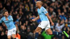 Indosport - Vincent Kompany terlalu bersemangat ketika mengangkat trofi Piala FA yang baru saja dimenangkan Manchester City pada hari Sabtu (18/05/19). Michael Regan/Getty Images.