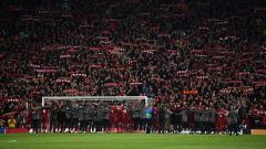 Indosport - Kebersamaan skuat Liverpool dan jajaran pelatih menyanyikan You Will Never Walk Alone bersama para suporter Stadion Anfield. Shaun Botterill /GettyImages.