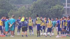 Indosport - Robert Rene Alberts memberikan arahan pada pemain Persib Bandung di bawah guyuran hujan
