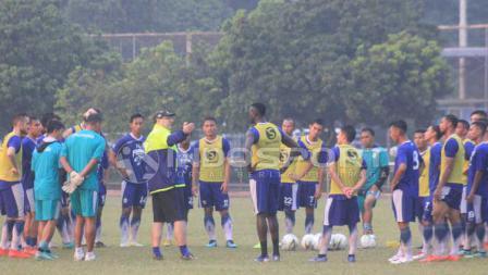Robert Rene Alberts memberikan arahan pada pemain Persib Bandung di bawah guyuran hujan