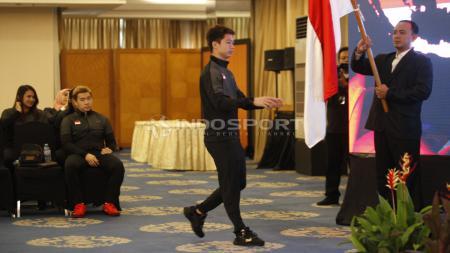 Pebulutangkis putra, Kevin Sanjaya melakukan prosesi mencium bendera Merah Putih pada acara pelepasan tim Piala Sudirman Indonesia di Hotel Atlet Century, Jakarta, Sabtu (10/05/19). Foto: Herry Ibrahim/INDOSPORT - INDOSPORT