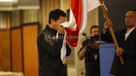 Pebulutangkis putra, Mohammad Ahsan melakukan prosesi mencium bendera Merah Putih pada acara pelepasan tim Piala Sudirman Indonesia di Hotel Atlet Century, Jakarta, Sabtu (10/05/19). Foto: Herry Ibrahim/INDOSPORT - INDOSPORT