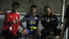 Indosport - Soni Setiawan usai menjalani perawatan medis, dan duduk di pinggri lapangan. Ronald Seger Prabowo/INDOSPORT