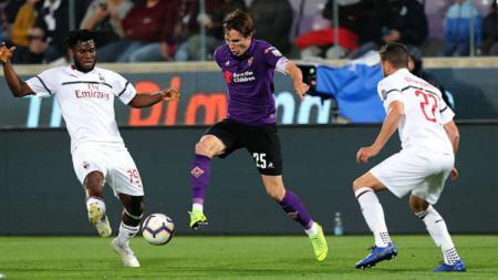 Pemain Fiorentina sedang melindungi bola dari rebutan pemain AC Milan. - INDOSPORT