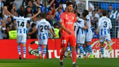 Indosport - Pemain Real Madrid tertunduk lesu saat Pemain Sociedad mencetak gol (ANDER GILLENEA/AFP/Getty Images).