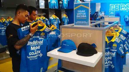 Dua orang Bobotoh sedang memilih jersey anyar Persib di Persib Merchandise Store, Jalan Sulanjana, Kota Bandung, Senin (13/05/2019). - INDOSPORT