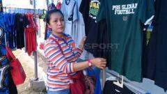 Indosport - Ibu Ana (40) penjual jersey dan syal asal Surabaya yang selalu berpindah-pindah stadion untuk berjualan.