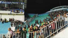 Indosport - Penjagaan ketat pihak kepolisian di antara tribun suporter PSS dan Arema FC.