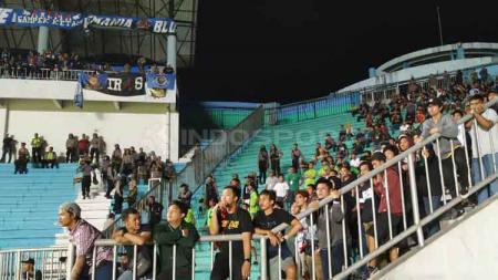 Penjagaan ketat pihak kepolisian di antara tribun suporter PSS dan Arema FC. - INDOSPORT
