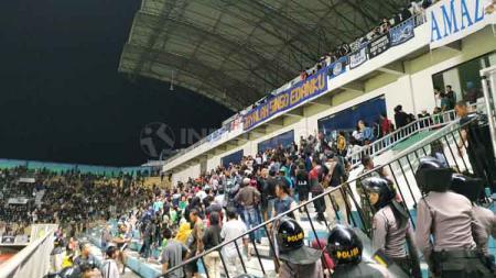 Penjagaan ketat pihak kepolisian di antara tribun suporter PSS Sleman dan Arema FC. - INDOSPORT