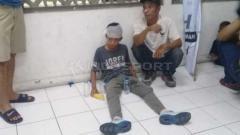Indosport - Salah satu bocah jadi korban pelemparan aksi suporter PSS Sleman vs Arema FC.