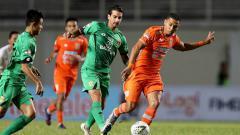 Indosport - Dua pemain Bhayangkara FC berusaha merebut bola dari kaki pemain Borneo FC.