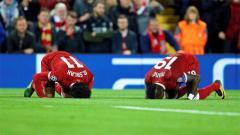 Indosport - Mohamed Salah dan Mane sujud usai Liverpool kalahkan Sevila di Liga Champions. Foto: dailysabah.com