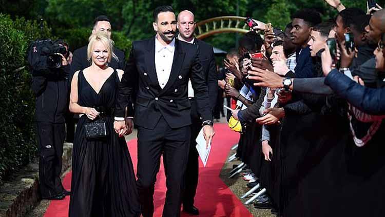 Bintang film Pamela Anderson bersama kekasihnya yang memperkuat Marseille, Adil Rami Copyright: AFP/Getty Images