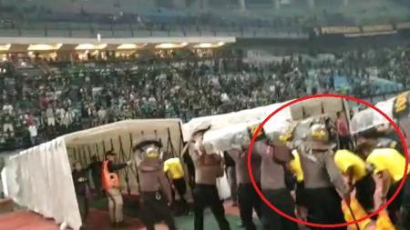 Suporter Persebaya melemparkan botol minuman ke arah lapangan sebagai bentuk ketidakpuasan atas kepemimpinan wasit. - INDOSPORT