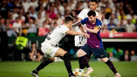 Lionel Messi tengah dikurung pemain Valencia dalam laga final Copa del Rey, Minggu (26/05/19) dini hari WIB. - INDOSPORT
