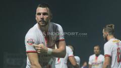 Indosport - Marko Simic menunjukkan badge juara Liga 1 saat melawan PSIS Semarang. Ronald S/INDOSPORT.COM