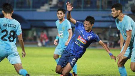 Duel pemain Arema FC, Dedik Setiawan dengan 3 pemain Persela Lamongan. Foto: Instagram@aremafcofficial - INDOSPORT