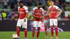 Indosport - Mesut Ozil, Pierre-Emerick Aubameyang dan Alexandre Lacazette tertunduk lesu.