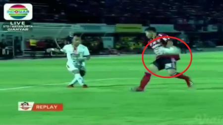 Cuplikan Handball yang dilakukan Ricky Fajrin di kotak penalti Bali United. - INDOSPORT