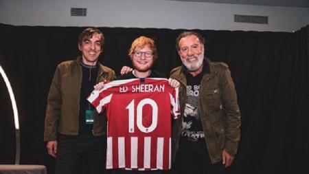 Ed Sheeran terlihat berfoto sambil membawa jersey Atletico Madrid. - INDOSPORT